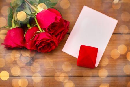 attentions: close up of gift box, red roses and greeting card on wood