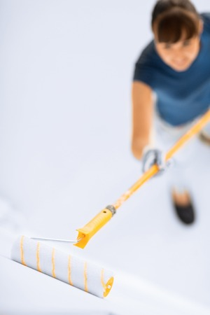 wall paint: woman with roller and paint colouring the wall Stock Photo