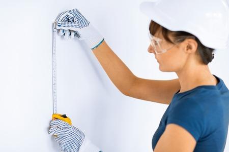 female architect: female architect measuring wall with flexible ruler Stock Photo