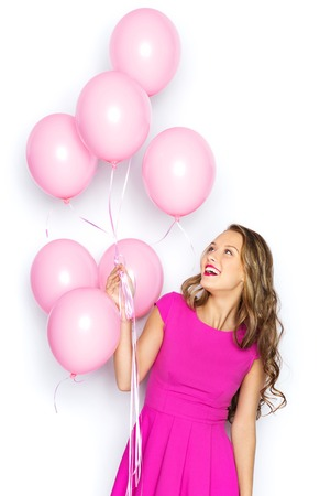 prom: happy young woman or teen girl in pink dress with helium air balloons