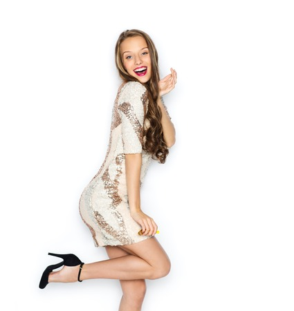 elegant party: happy young woman or teen girl in fancy dress with sequins and long wavy hair posing