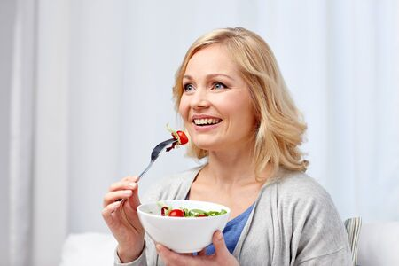 age: smiling young woman eating vegetable salad at home