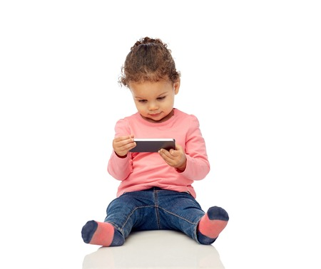 multiracial children: smiling little african american baby girl playing with smartphone and sitting on floor