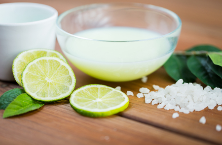 cosmetics products: close up of citrus body lotion in glass bowl and sea salt with limes on wooden table
