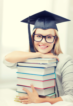 birretes: picture of happy student in graduation cap with stack of books Foto de archivo