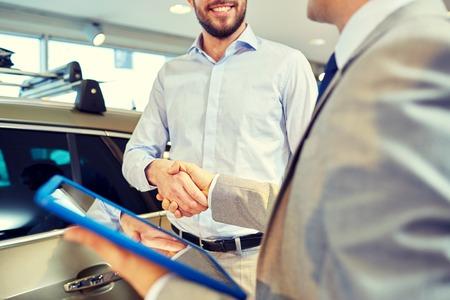 alzando la mano: cerca del hombre y distribuidor de coche feliz con el ordenador Tablet PC estrechan la mano en salón del automóvil o salón de belleza Foto de archivo