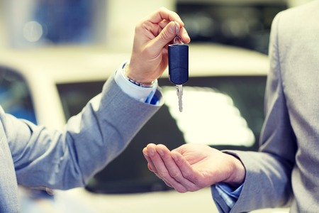 close up of male hands with car key in auto show or salon