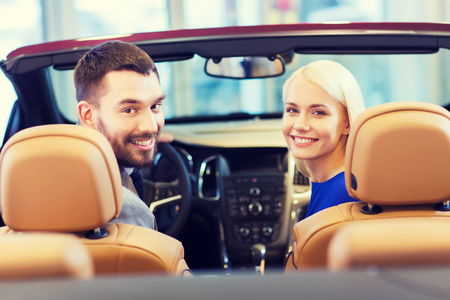 buyers: happy couple sitting in car at auto show or salon