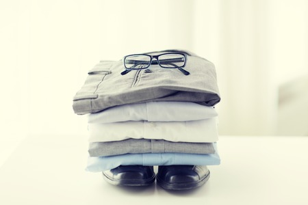 ironed: close up of ironed and folded shirts and formal shoes on table at home