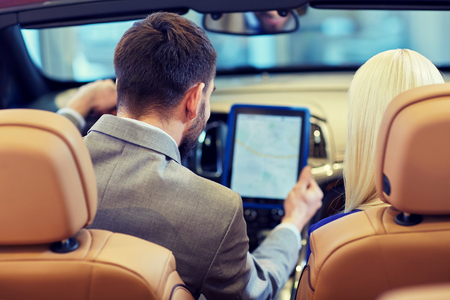 car shop: close up of couple sitting in cabriolet car with tablet pc computer at auto show or salon from back Stock Photo