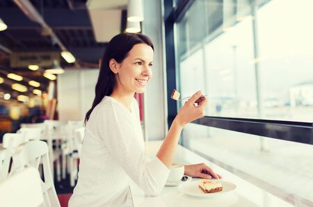 woman eating cake: smiling young woman eating cake and drinking coffee at cafe Stock Photo
