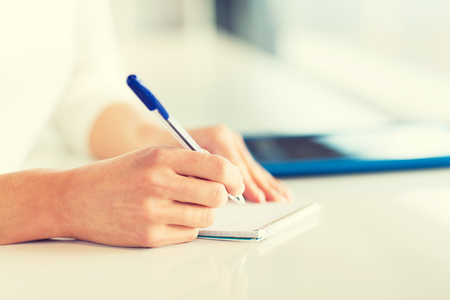 Office women: close up of woman hands with pen writing to notepad