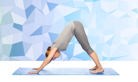 dog pose: woman making yoga in downward facing dog pose on mat over low poly background