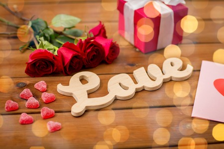 attentions: close up of word love, gift box, red roses and greeting card with heart-shaped candies and golden lights on wood
