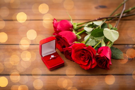 flirtation: close up of gift box with diamond engagement ring and red roses on wood Stock Photo