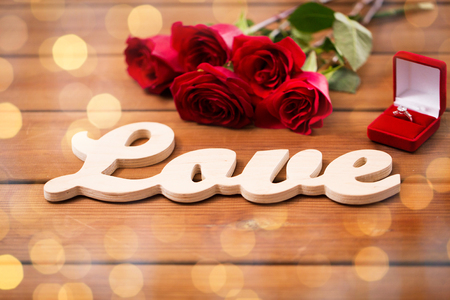 uprzejmości: close up of gift box with diamond engagement ring, red roses and word love on wood over golden lights