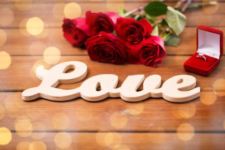 uprzejmości: zamknąć pudełko z pierścionek zaręczynowy diament, czerwonych róż i słowo miłość na drewnie nad Złotego świateł