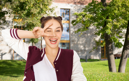 summer sign: happy smiling pretty teenage student girl showing peace sign and winking over summer campus background