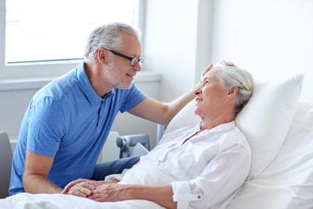 happy senior man visiting and cheering his woman lying in bed at hospital ward