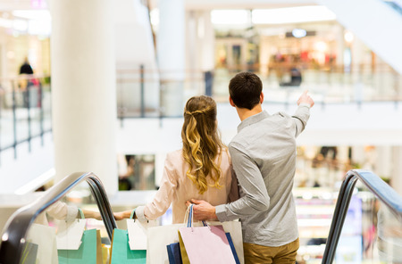 direction of: happy young couple with shopping bags going down by escalator and pointing finger in mall