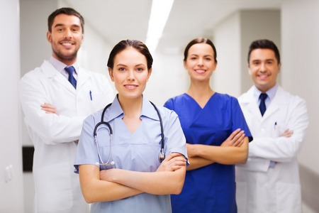 medics: clinic, profession, people, health care and medicine concept - happy group of medics or doctors at hospital corridor Stock Photo