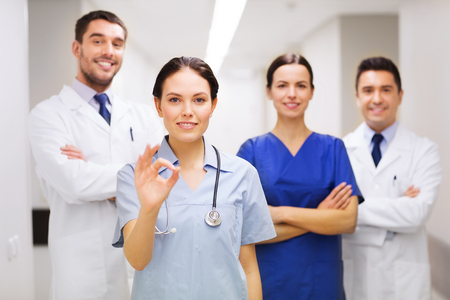 medics: group of happy medics or doctors at hospital corridor showing ok hand sign Stock Photo