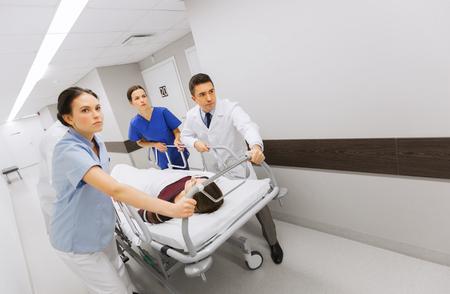 groep van artsen of artsen dragen bewusteloze vrouw patiënt op ziekenhuisgurney tot de noodhulpdiensten Stockfoto