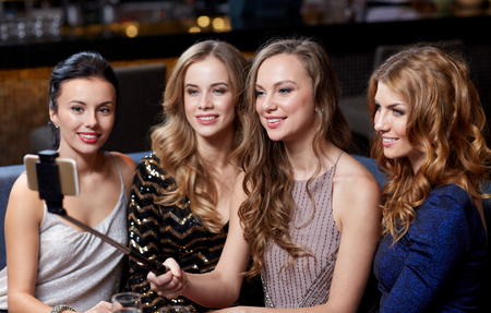 night stick: happy women with smartphone selfie stick taking picture at night club Stock Photo