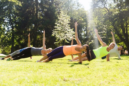 group of happy teenage friends or sportsmen exercising at boot camp Stock Photo