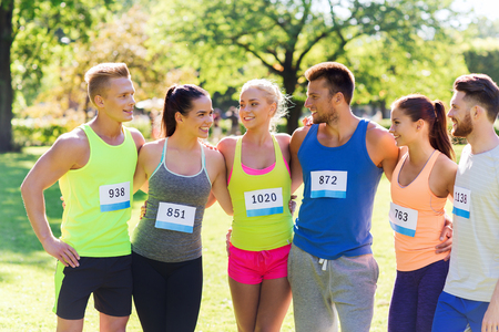 sportsmen: group of happy teenage friends or sportsmen couple with racing badge numbers outdoors Stock Photo