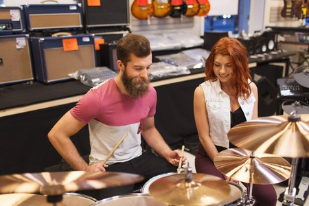 cymbals: happy man and woman playing cymbals at music store