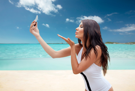 beach kiss: summer, travel, technology and people concept - sexy young woman taking selfie with smartphone and sending blow kiss over tropical beach over tropical beach background Stock Photo