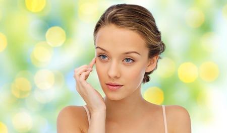 la beauté, les gens, les cosmétiques, les soins de la peau et le concept de la santé - jeune femme d'appliquer la crème sur son visage sur fond vert lumières fond Banque d'images