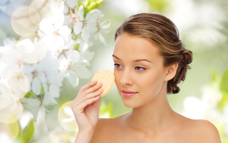 natural face: beauty, people and skincare concept - young woman cleaning face with exfoliating sponge over green natural cherry blossom background Stock Photo