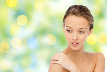bare woman: beauty, people, body care and health concept - smiling young woman face and hand on bare shoulder over green lights background