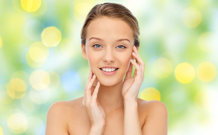 beauty, people and health concept - smiling young woman with bare shoulders touching her face over green lights background Stock Photo