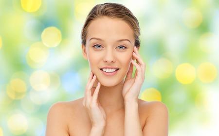 sonriente: la belleza, la gente y el concepto de salud - sonriendo mujer joven con los hombros descubiertos que toca su cara sobre el fondo verde de las luces Foto de archivo