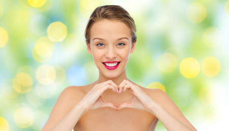 natural face: beauty, people, love, valentines day and make up concept - smiling young woman with pink lipstick on lips showing heart shape hand sign over green lights background Stock Photo
