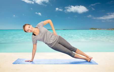 beach mat: fitness, sport, people and healthy lifestyle concept - woman making yoga in side plank pose on mat over beach background Stock Photo