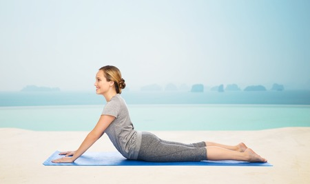 dog pose: fitness, sport, people and healthy lifestyle concept - woman making yoga in dog pose on mat over infinity edge pool at hotel resort background
