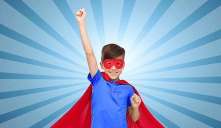 carnival, childhood, power, gesture and people concept - happy boy in red super hero cape and mask showing fists over blue burst rays background Stock Photo