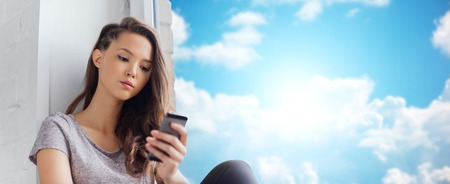woman cell phone: people, technology and teens concept - sad unhappy pretty teenage girl sitting on windowsill with smartphone and texting over blue sky and clouds background
