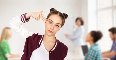 estudiantes de secundaria: la gente, la escuela, la educación, el estrés y el concepto de los adolescentes - aburrido chica estudiante adolescente haciendo tiro en la cabeza por el gesto del arma del dedo sobre el fondo del aula con el profesor y compañeros