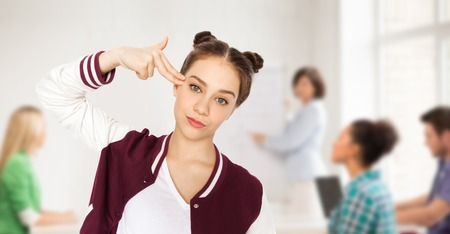 bore: people, school, education, stress and teens concept - bored teenage student girl making headshot by finger gun gesture over classroom background with teacher and classmates