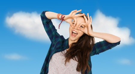 making face: people and teens concept - happy smiling pretty teenage girl making face and having fun over blue sky and clouds background