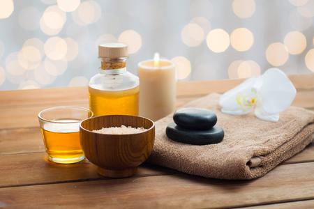 belleza, spa, cuidado del cuerpo, cosméticos naturales y concepto - Cierre de sal rosa con aceite de masaje y toalla de baño en la mesa de madera
