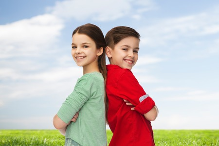 brothers: childhood, summer and people concept - happy smiling boy and girl standing back to back over blue sky and grass background