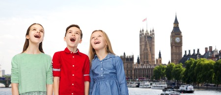 nice girl: childhood, travel, tourism, friendship and people concept - happy amazed boy and girls looking up with open mouths over london city background