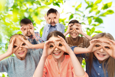 childhood, summer, friendship and people concept - happy children making faces and having fun over green natural background Imagens