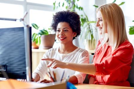 bedrijfsleven, onderwijs, opstarten en mensen concept - happy vrouwen of studenten met een computer in het kantoor Stockfoto